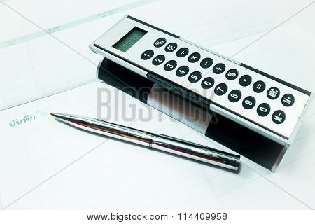 Pocket Calculator And Pen On The Table