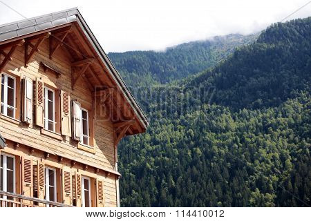 Traditional European Alpine Ski Chalet Hotel, View Of The Alps In The Distance.