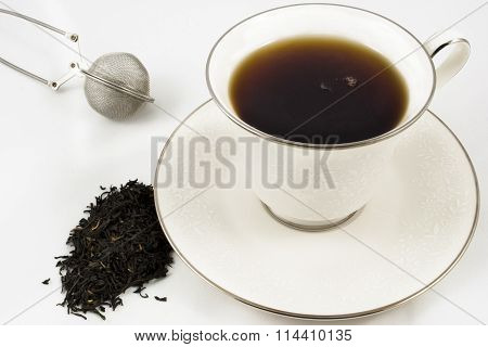 Cup Of Black Tea With Leaves And Strainer