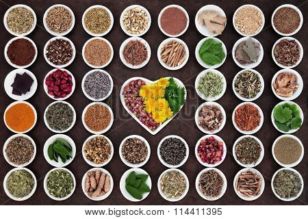 Herbal medicine selection used for womans health in heart and round shaped porcelain bowls over lokta paper background.