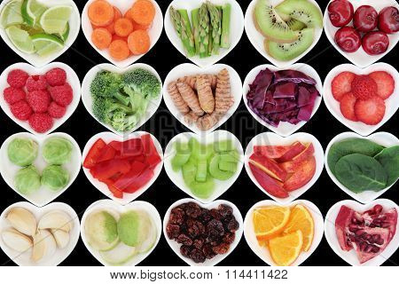 Superfood vegetable and fruit selection in heart shaped porcelain dishes over black background, high in vitamins and antioxidants.