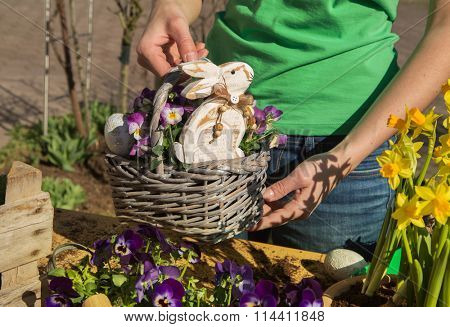 Easter handmade decoration with spring flowers and bunny at home in the garden.