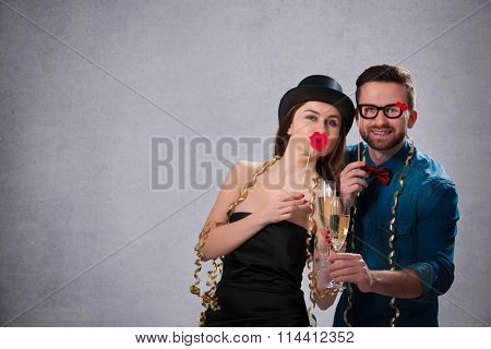 Young couple with champagne flutes celebrating New year's eve and having fun