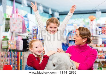 Little child riding on stuffed animal in toy store raising her hands in excitement