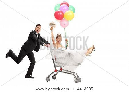 Full length portrait of a groom pushing the bride in a shopping cart isolated on white background