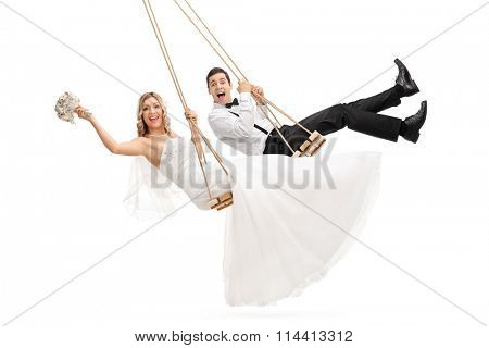 Studio shot of young groom and a bride swinging on wooden swings isolated on white background