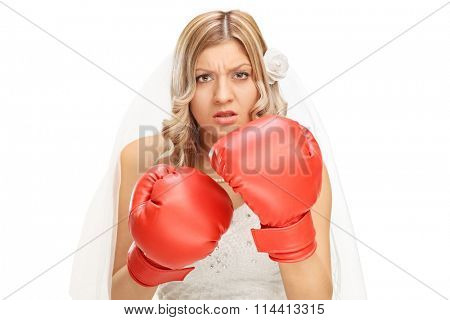 Studio shot of an angry young bride with red boxing gloves on her hands isolated on white background