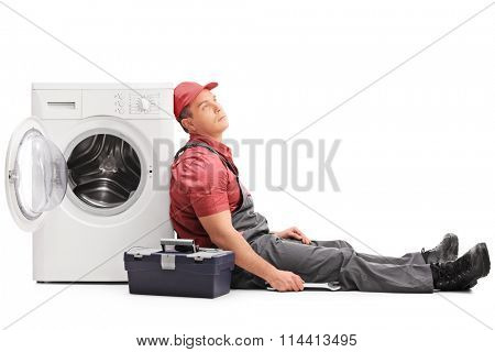 Exhausted young plumber sitting by a washing machine and looking up isolated on white background