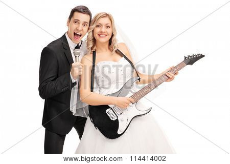 Joyful newlywed couple having fun and playing music isolated on white background
