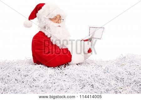 Studio shot of Santa Claus cutting a letter with scissors and standing in a pile of shredded paper isolated on white background