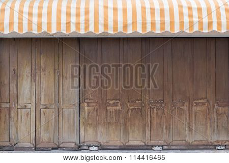 Vintage Wooden Gate With Yellow Stripe Awning