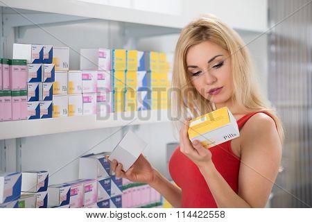 Beautiful Woman Examining Capsule Packet
