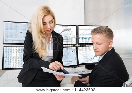 Financial Analysts Discussing Over Documents In Office