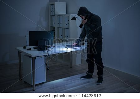 Robber With Flashlight Holding Laptop At Desk
