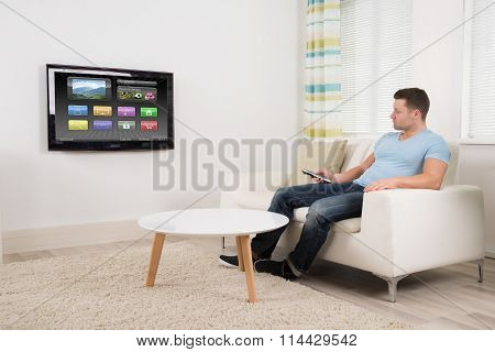 Man With Remote Control Watching Television At Home
