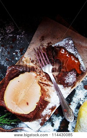 Pear pie sprinkled with powdered sugar on a black background. Beautiful chocolate pear tart in secti