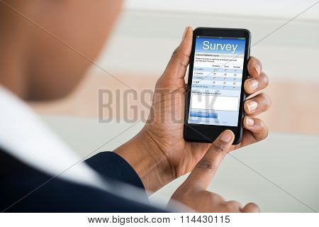 Businesswoman Filling Survey Form On Mobile Phone