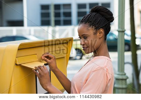 Woman Inserting Letter In Mailbox