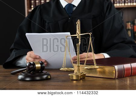 Judge Reading Documents At Desk In Courtroom