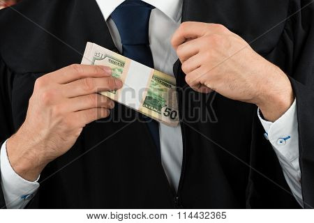 Judge Putting Dollar Bundle In Pocket