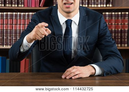 Lawyer Arguing While Sitting At Desk