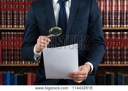 Lawyer Examining Legal Documents With Magnifying Glass