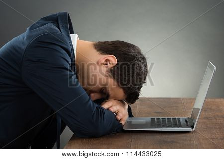 Exhausted Businessman Leaning On Desk