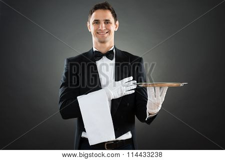 Portrait Of Happy Waiter With Empty Tray And Towel