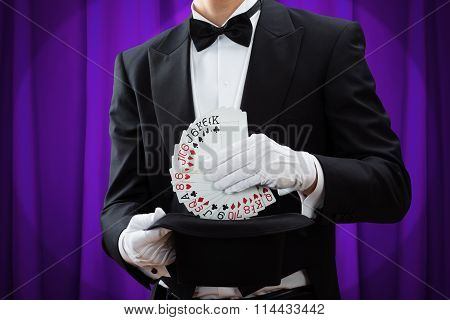Magician Putting Playing Cards In Hat