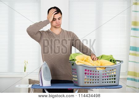 Tired Man Looking At Laundry Basket