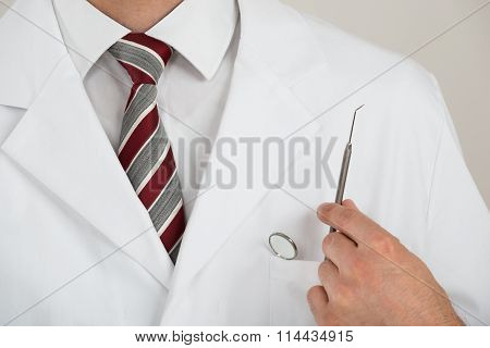 Midsection Of Dentist With Tools In Pocket