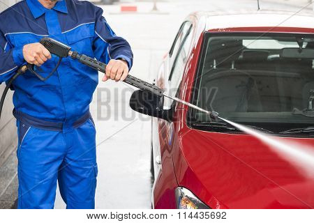 Worker Cleaning Car With Jet Sprayer At Service Station