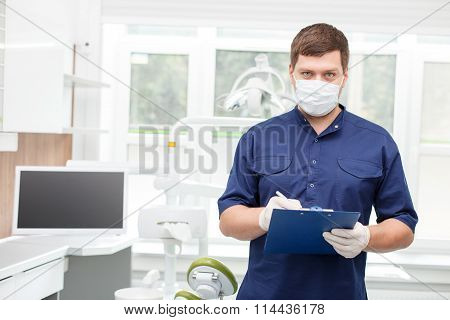 Attractive young dentist is working in his cabinet