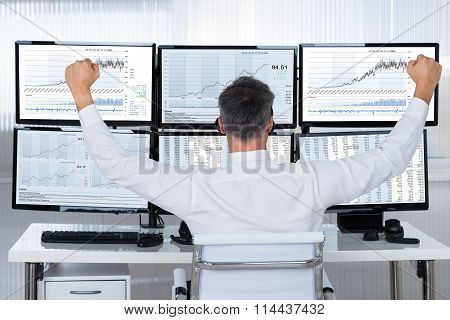 Successful Trader With Arms Raised Looking At Graphs On Screens