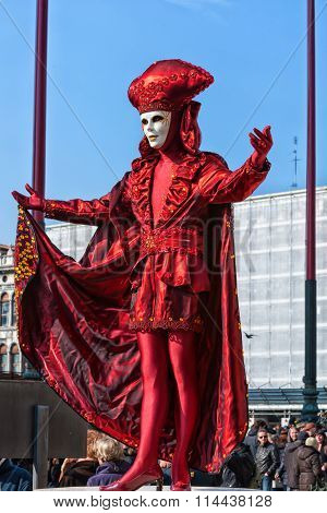 Venetian Mask in beautiful red costume at Venice Carnival
