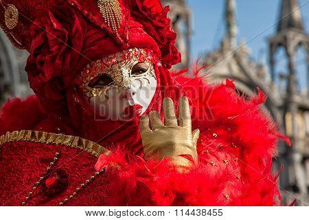 Venetian Mask in beautiful red costume at Carnival in Venice