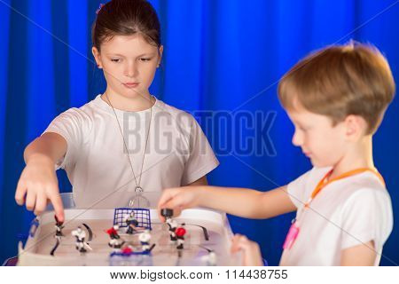 Boy And Girl Playing Table Hockey.