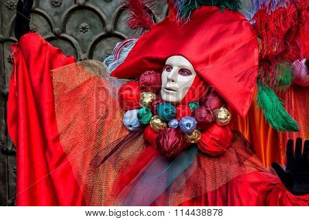 Venetian Mask in beautiful red costume at Carnival in Venice