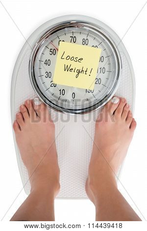 Woman Standing On Weight Scale With Loose Weight Note
