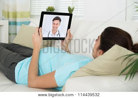 Pregnant Woman Video Conferencing With Male Doctor