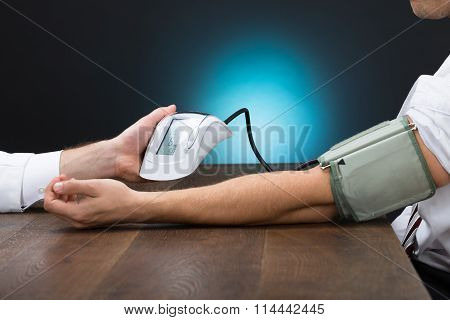 Doctor Checking Blood Pressure Of Businessman At Table