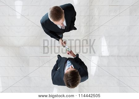 Businessman Bribing Colleague In Office