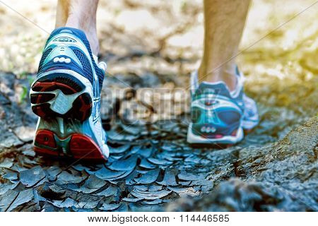 Runner Feet Running On Crack Road Closeup On Shoes. Man Fitness Extreme Jog Workout Welness Concept
