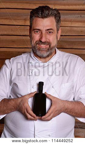 Businessman chef holding extra virgin olive oil bottle