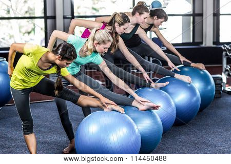 Fit smiling group doing exercise with exercise balls in gym