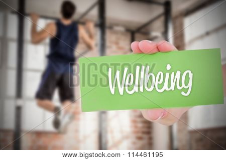 The word wellbeing and hand showing card against