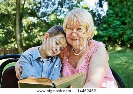 Smiling Boy And His Grandmother Reading A Book In The Park