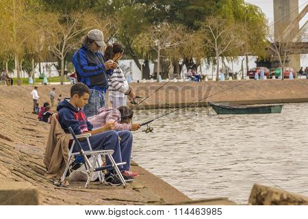 Family Fishing At The Coast Of River In Montevideo