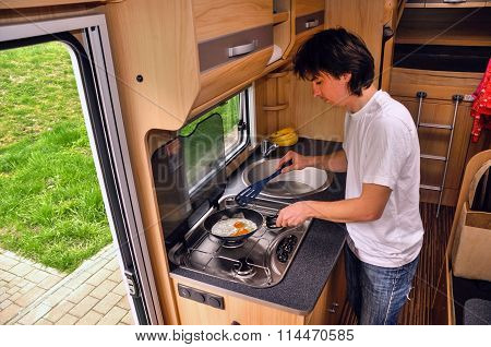 Family vacation, RV holiday trip, man cooking in camper. Motorhome interior