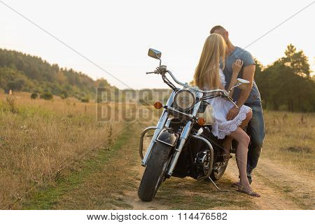 Young romantic couple in a field on a motorcycle